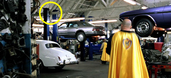 Man in yellow cape walking in car body shop with BendPak two-post lift in background