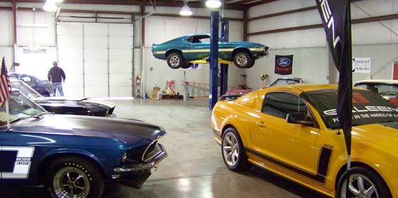 Classic cars in a shop with a BendPak two-post lift