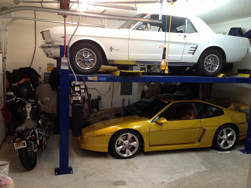 Yellow car under and white car over on blue BendPak four-post car lift